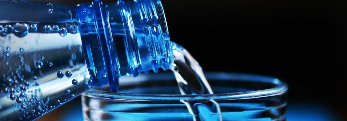 Image d'une bouteille d'eau versée dans un verre - Crédit Eau Famille Nombreuse